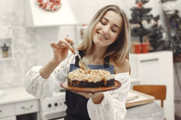 Jovem segurando um bolo caseiro na cozinha Foto gratuita