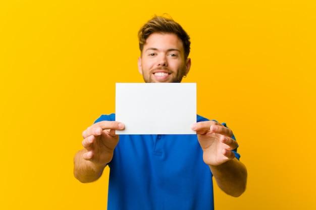 Jovem, segurando um cartaz contra fundo laranja Foto Premium