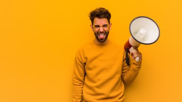 Jovem, segurando um megafone funnny e língua mostrando amigável Foto Premium