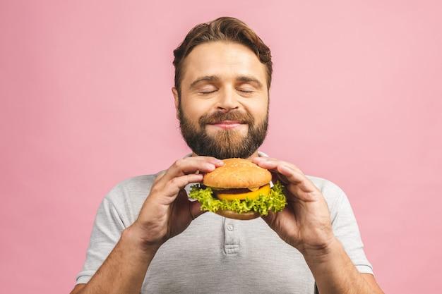 Jovem, segurando um pedaço de hambúrguer Foto Premium