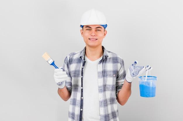 Jovem, segurando um pincel e tinta balde Foto gratuita