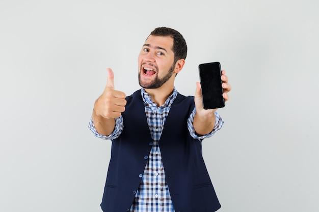 Jovem segurando um telefone celular, mostrando o polegar na camisa Foto gratuita