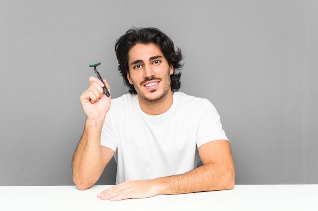 Jovem, segurando uma lâmina de barbear feliz, sorridente e alegre. Foto Premium