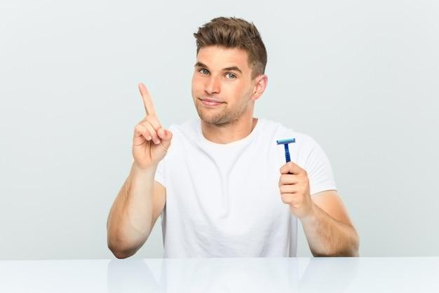 Jovem, segurando uma lâmina de barbear, mostrando o número um com o dedo. Foto Premium