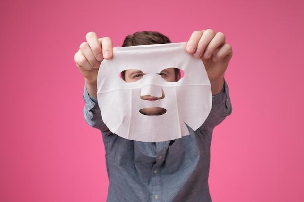 Jovem segurando uma máscara cosmética perto da câmera Foto Premium