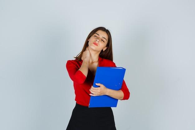 Jovem segurando uma pasta enquanto mantém a mão no pescoço em uma blusa vermelha Foto gratuita