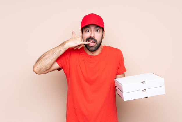 Jovem, segurando uma pizza, fazendo gesto de telefone e duvidando Foto Premium