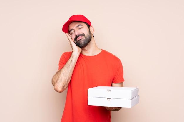 Jovem, segurando uma pizza, fazendo o gesto do sono em expressão dorable Foto Premium