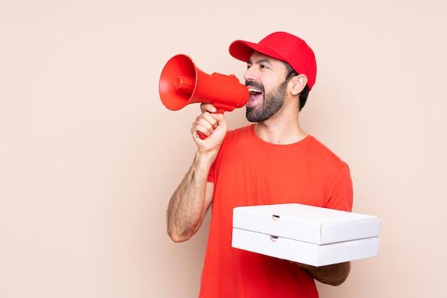 Jovem, segurando uma pizza sobre fundo isolado, gritando através de um megafone Foto Premium