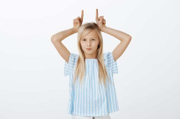 Jovem sendo teimosa, não tendo respeito pelos adultos. retrato de filha fofa confiante indiferente com cabelo loiro, segurando o dedo indicador na cabeça, imitando chifres e sorrindo Foto gratuita
