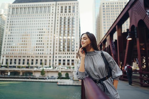 Jovem senhora atravessando a ponte da cidade Foto gratuita