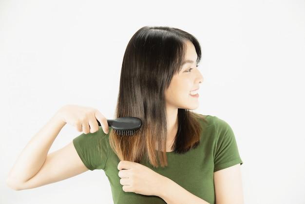 Jovem senhora bonita feliz usando o pente para reta seu cabelo - conceito de cuidado de cabelo de beleza de mulher Foto gratuita