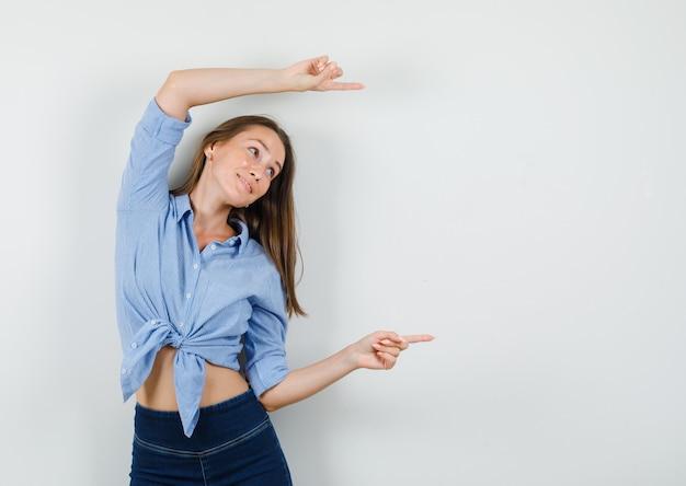 Jovem senhora de camisa azul, calça apontando para fora e parecendo alegre Foto gratuita
