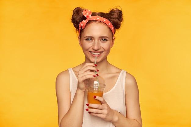 Jovem senhora, linda mulher ruiva com dois pãezinhos e faixa de cabelo parecendo feliz. vestindo camisa branca e segurando seu smoothie saudável. sorrindo assistindo isolado na parede amarela Foto gratuita