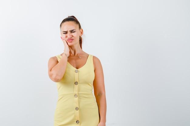 Jovem senhora sofre de dor de dente em um vestido amarelo e parece dolorida. vista frontal. Foto gratuita
