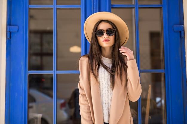 Jovem senhora vestida casual com casaco brilhante chapéu e óculos de sol está em frente a porta azul Foto gratuita