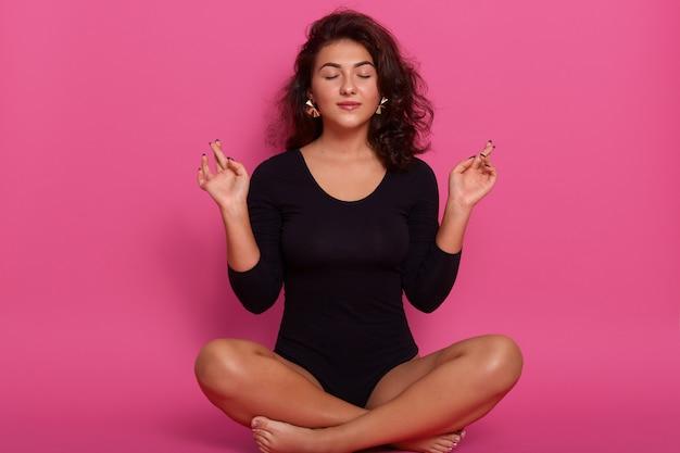 Jovem sentada em posição de lótus, com os olhos fechados, fazendo yoga, relaxando em casa, vestindo preto combidress, tendo cabelos ondulados, sentada no chão na parede concentrada rosa. Foto gratuita