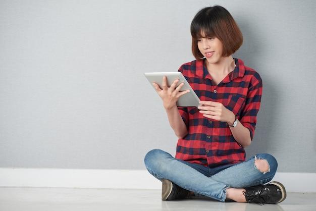 Jovem sentada na posição de lótus, navegando na net em seu digital tablet pc Foto gratuita