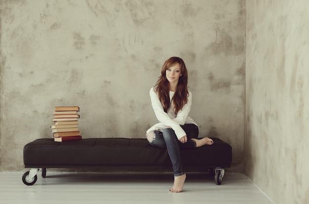 Jovem sentada no banco da sala Foto gratuita