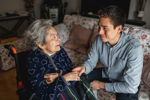Jovem sentado ao lado de uma senhora idosa e doente em cadeira de rodas, segurando suas mãos enquanto fala e sorri. família, conceito de atendimento domiciliar. Foto Premium
