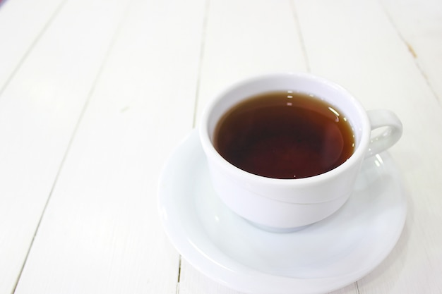Jovem sentado caffe tomando café da manhã waffle com calda de chocolate, fatias de banana e morangos no prato de cerâmico verde e fotografou seu café da manhã Foto gratuita