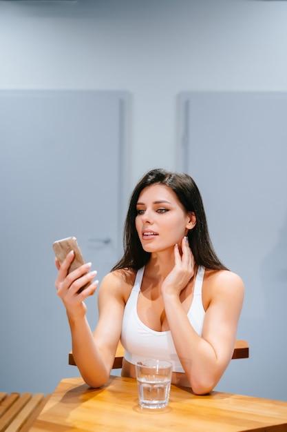 Jovem sentado e usando o smartphone após o treino Foto gratuita