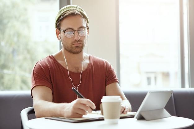 Jovem sentado em um café ouvindo música Foto gratuita