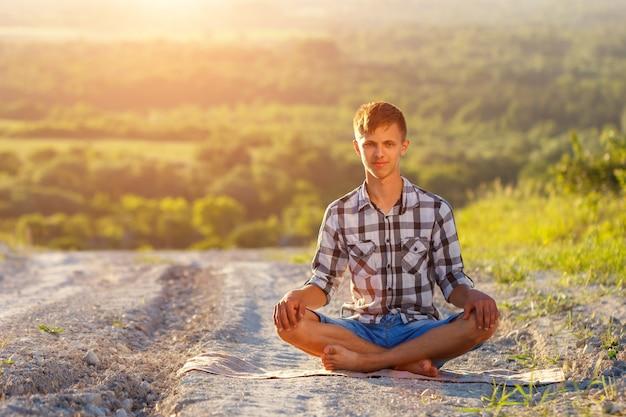 Jovem sentado na estrada em posição de lótus em um dia ensolarado Foto Premium