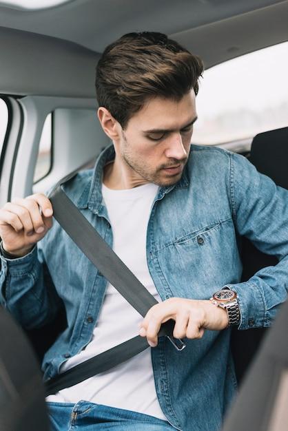 Jovem sentado no carro prende o cinto de segurança Foto gratuita