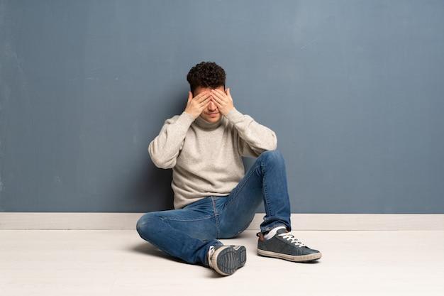 Jovem sentado no chão cobrindo os olhos pelas mãos Foto Premium