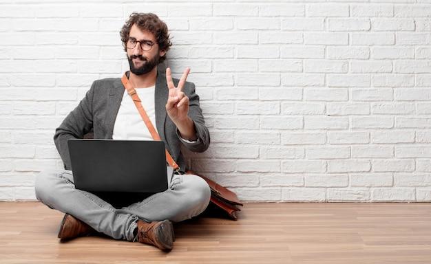 Jovem sentado no chão com uma expressão orgulhosa, feliz e confiante Foto Premium
