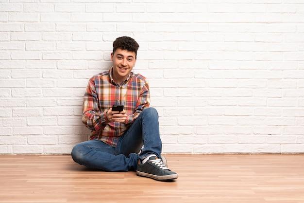 Jovem sentado no chão, enviando uma mensagem com o celular Foto Premium
