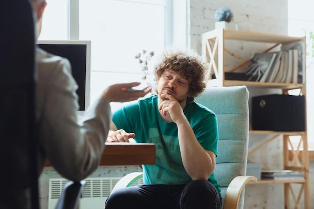 Jovem sentado no escritório durante a entrevista de emprego com funcionária, chefe ou gerente de rh, conversando, pensando, parece confiante Foto gratuita