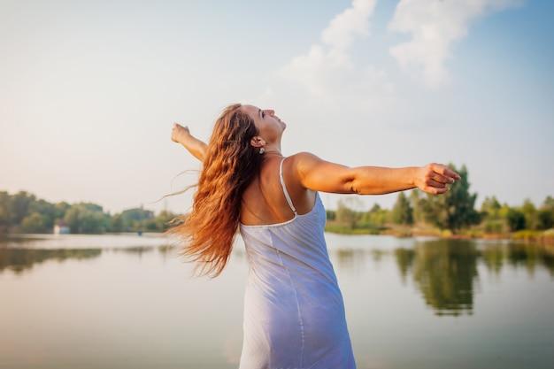 Jovem, sentindo-se livre e feliz, levantando os braços e girando pelo rio verão Foto Premium