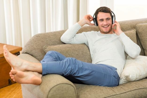 Jovem, sentindo-se relaxado enquanto ouve música com fones de ouvido na sala de estar Foto Premium