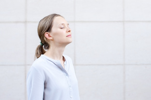 Jovem serena com olhos fechados meditando Foto Premium