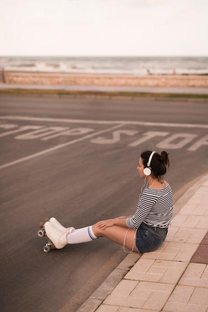 Jovem, skater feminino, escutar música, ligado, headphone, sentar calçada, à margem estrada Foto gratuita