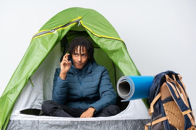 Jovem sleepeng em um acampamento sobre parede isolada Foto Premium