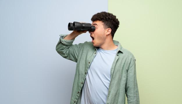 Jovem, sobre, azul verde, e, olhando ao longe, com, binóculos Foto Premium