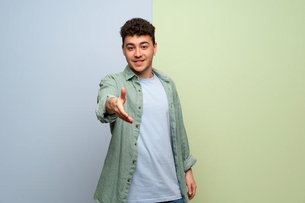 Jovem sobre fundo azul e verde, apertando as mãos para fechar um bom negócio Foto Premium