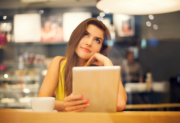 Jovem sonhando em um café Foto gratuita