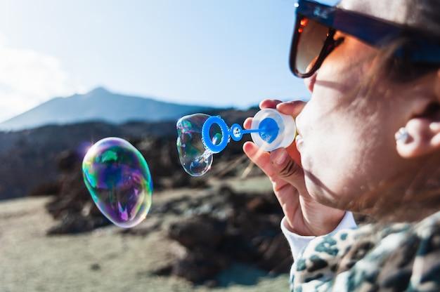 Jovem, soprando bolhas de sabão Foto Premium