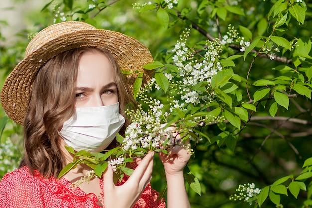 Jovem, soprando nariz e espirros em tecido na frente da árvore florescendo. alérgenos sazonais que afetam as pessoas. bela dama tem rinite. Foto Premium
