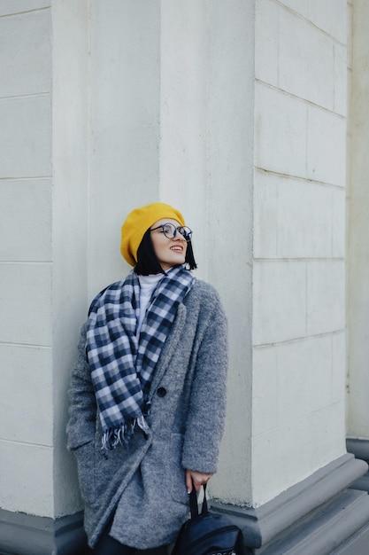 Jovem sorridente atraente em copos no casaco e boina amarela sobre um fundo claro simples Foto Premium