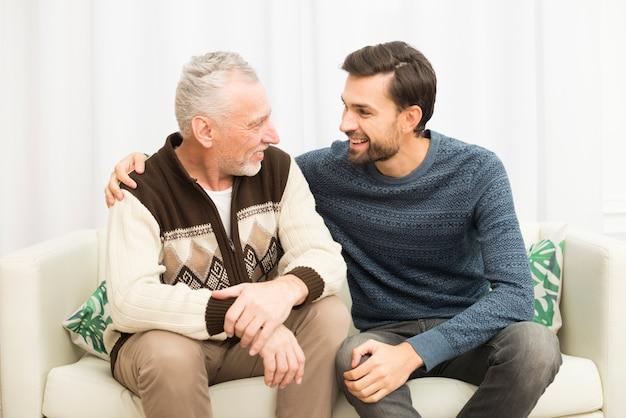 Jovem sorridente cara abraçando homem envelhecido no sofá Foto gratuita