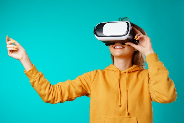 Jovem sorridente casual usando óculos de realidade virtual contra o azul Foto Premium
