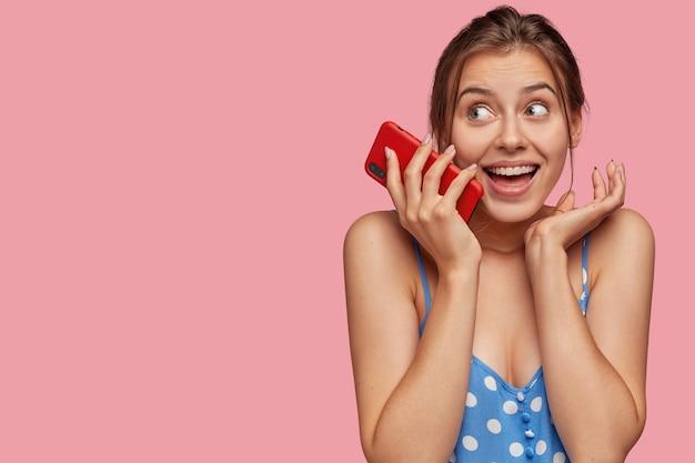 Jovem sorridente e encantada mantendo o smartphone vermelho moderno perto do rosto Foto gratuita