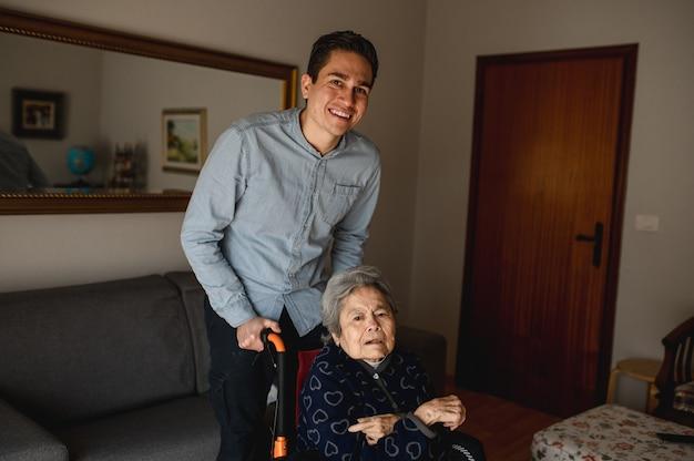 Jovem sorridente empurrando a cadeira de rodas com uma mulher idosa e doente. família, conceito de atendimento domiciliar. Foto Premium