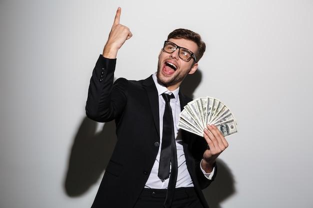 Jovem sorridente homem bonito terno preto clássico segurando o monte de dinheiro enquanto aponta com o dedo para cima Foto gratuita