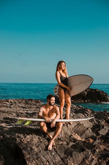Jovem sorridente homem e mulher com pranchas de surf na rocha perto do mar Foto gratuita